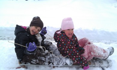 Girls ready to sled in the snow.