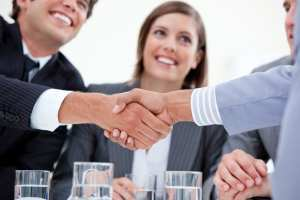 Smiling business people closing a deal by shaking hands