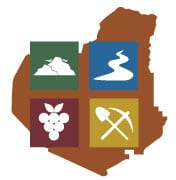 Lumpkin County Development authority logo, featuring 4 different colored blocks, with symbols of a mountain, a road, a grape vine, and a pick ax.