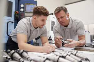 one male Engineer Showing a male Apprentice How To operate a piece of equipment