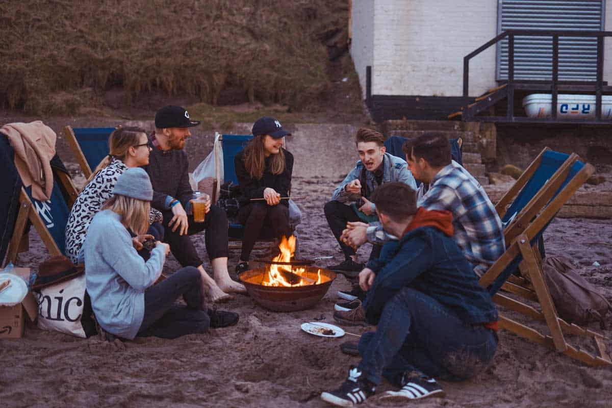 Group of friends sitting around a bonfire on the beach.
