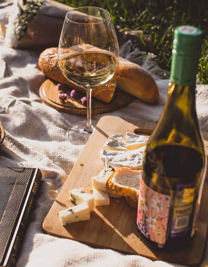 Wine and cheese on a picnic blanket.