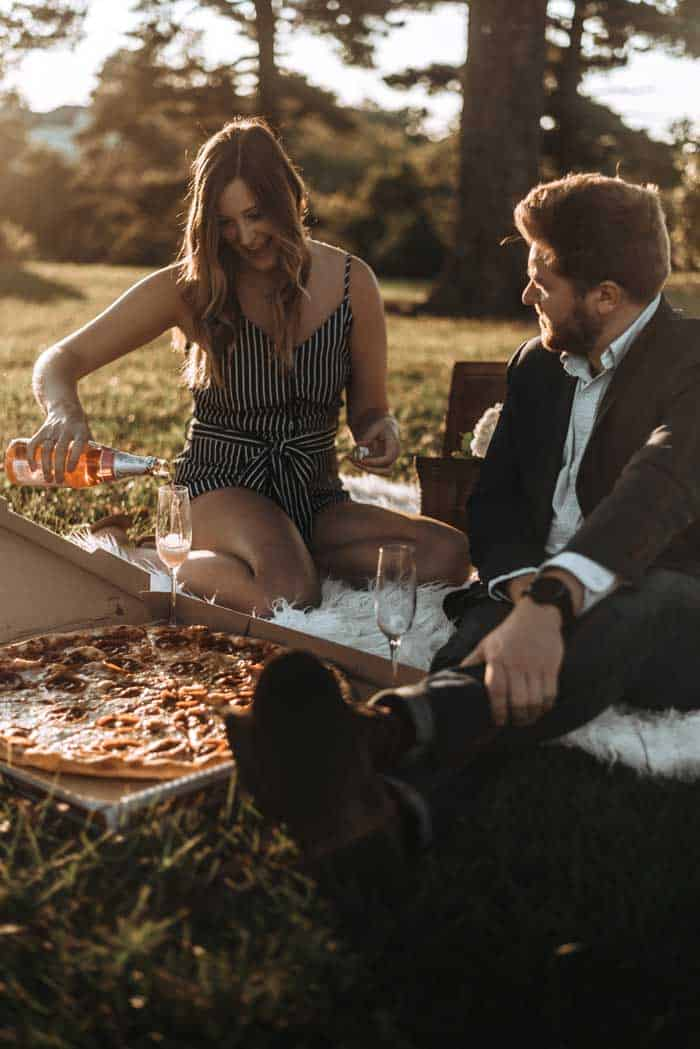 Couple enjoying champagne and pizza on a rug in the park.