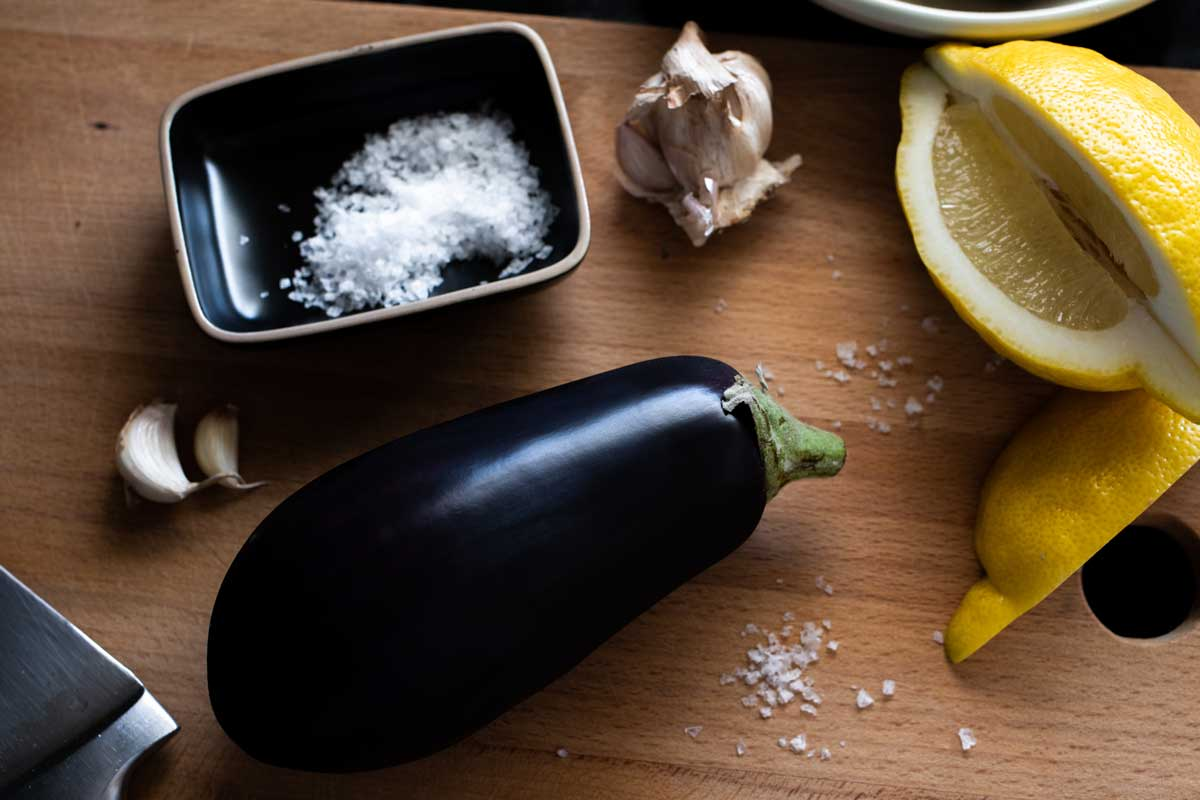 Whole eggplant on wooden board with lemon wedge, garlic cloves, and sea salt.