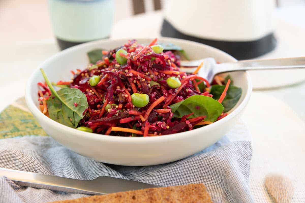 Bowl of shredded beetroot salad with bright green beans.