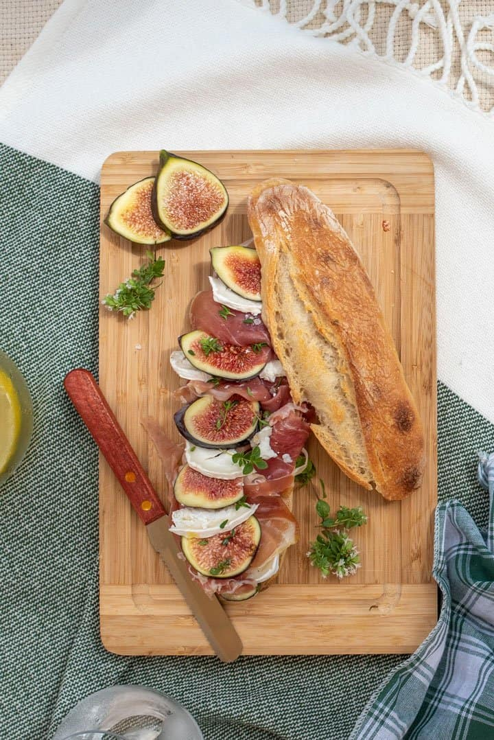 Baguette with prosciutto and figs on a wooden board.