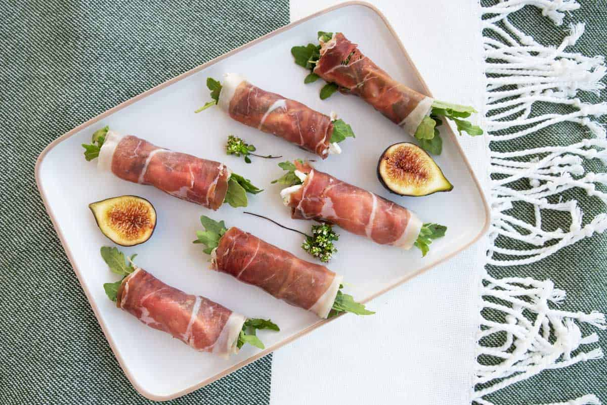 Plate of prosciutto rolls stuffed with figs and goats cheese.