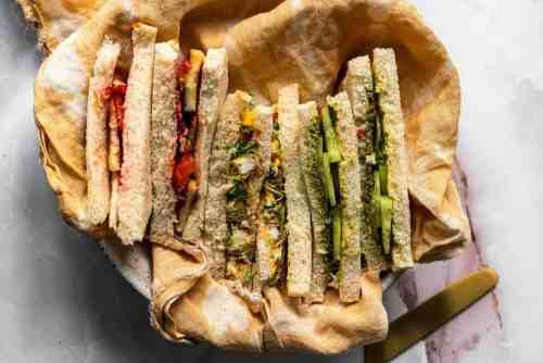 Indian style tea sandwiches in a basket with a cloth napkin.