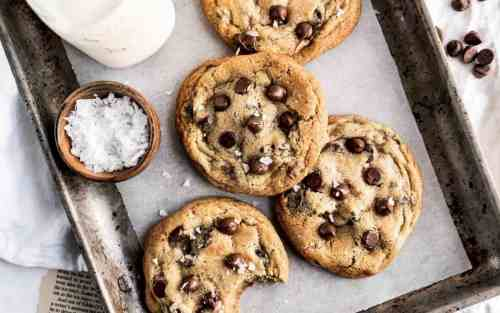 A tray of freshly baked chocolate chip cookies with a side bowl of flaky salt.