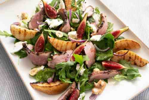 Plate of colourful smoked duck and grilled pear salad.