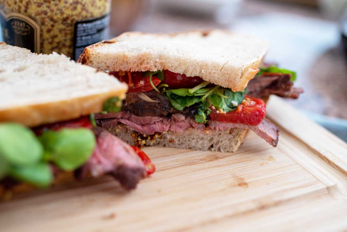 Roast beef sandwich with roasted vine tomatoes cut in half.