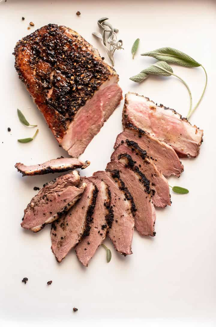 Smoked duck breast on a plate with thin slices fanned out in front.