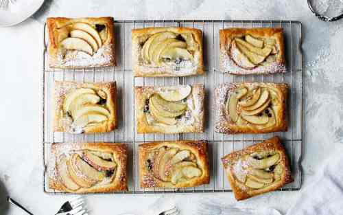 Apple tarts on a baking tray dusted with sugar. A perfectly portable picnic dessert.