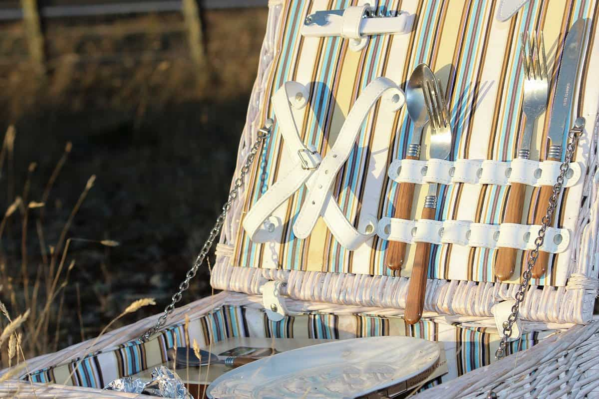 Close up of open white wicker picnic basket in a field with cutlery in the place holders inside the lid.