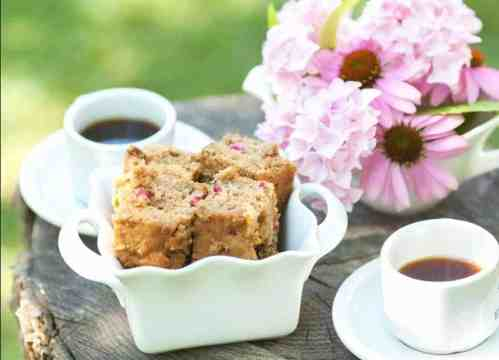 Sweet zucchini bread in a picnic scene with coffee and flowers.