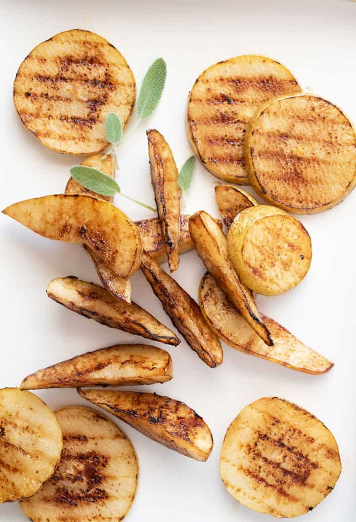 Grilled pear slices and wedges with small sage leaves.