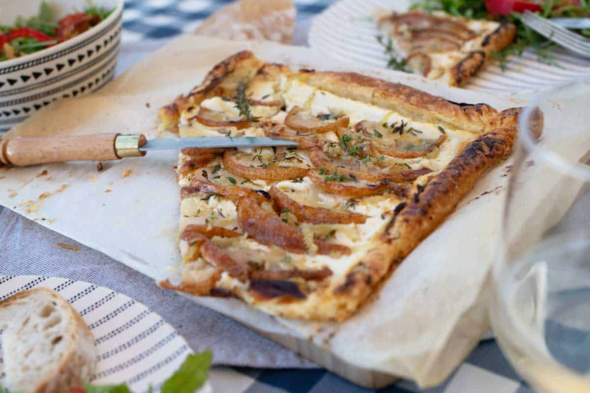 Pear and ricotta tart on a table with salads and wine.