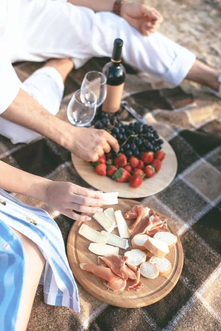 Plates of cheese and fruits with wine on a picnic blanket.
