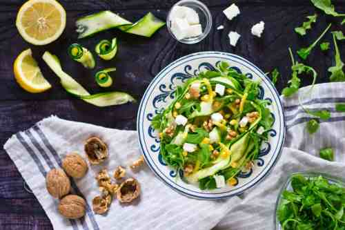 Zucchini salad on a black table with ingredients scattered around.