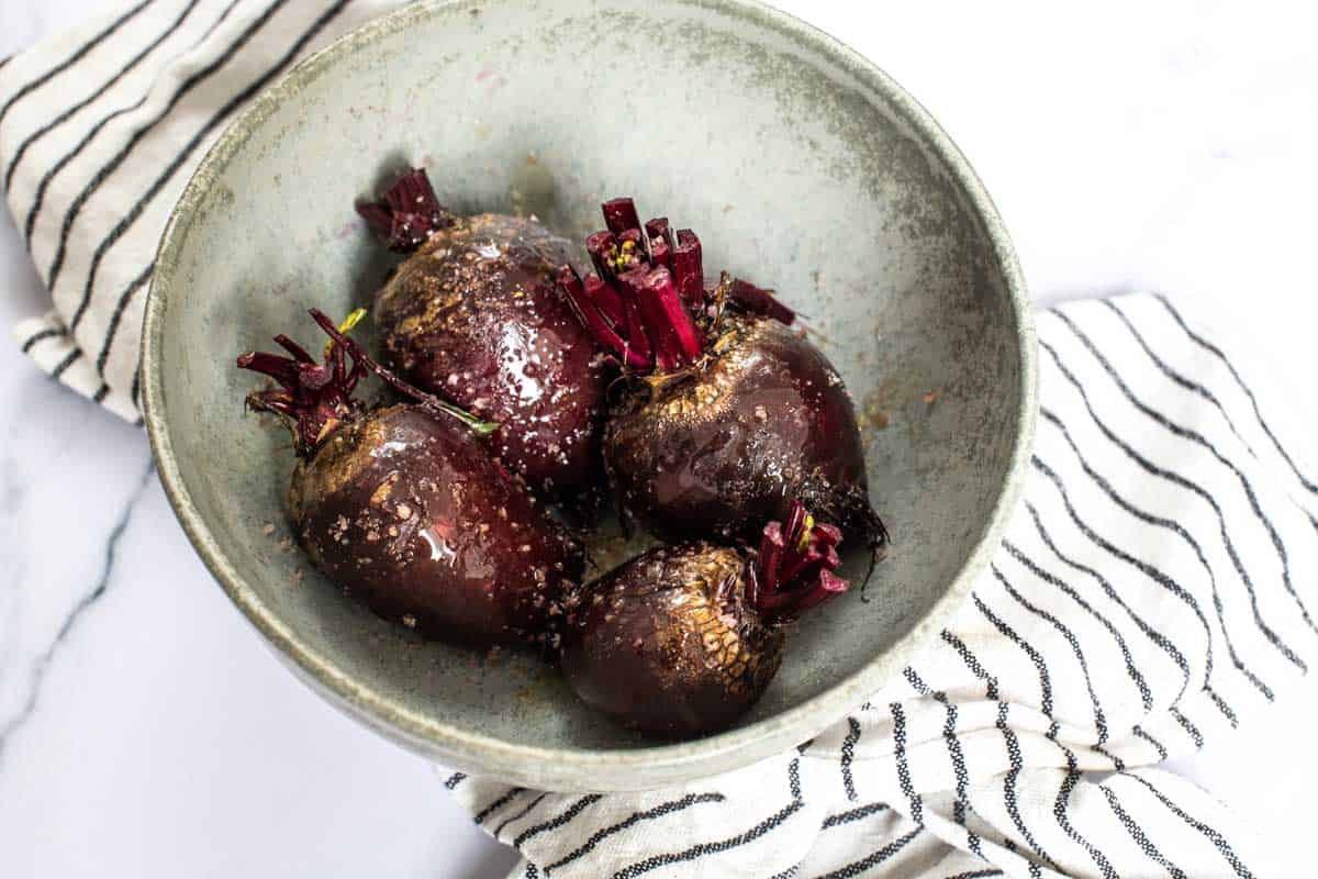 Bowl of raw beets dressed in oil and salt ready for roasting.