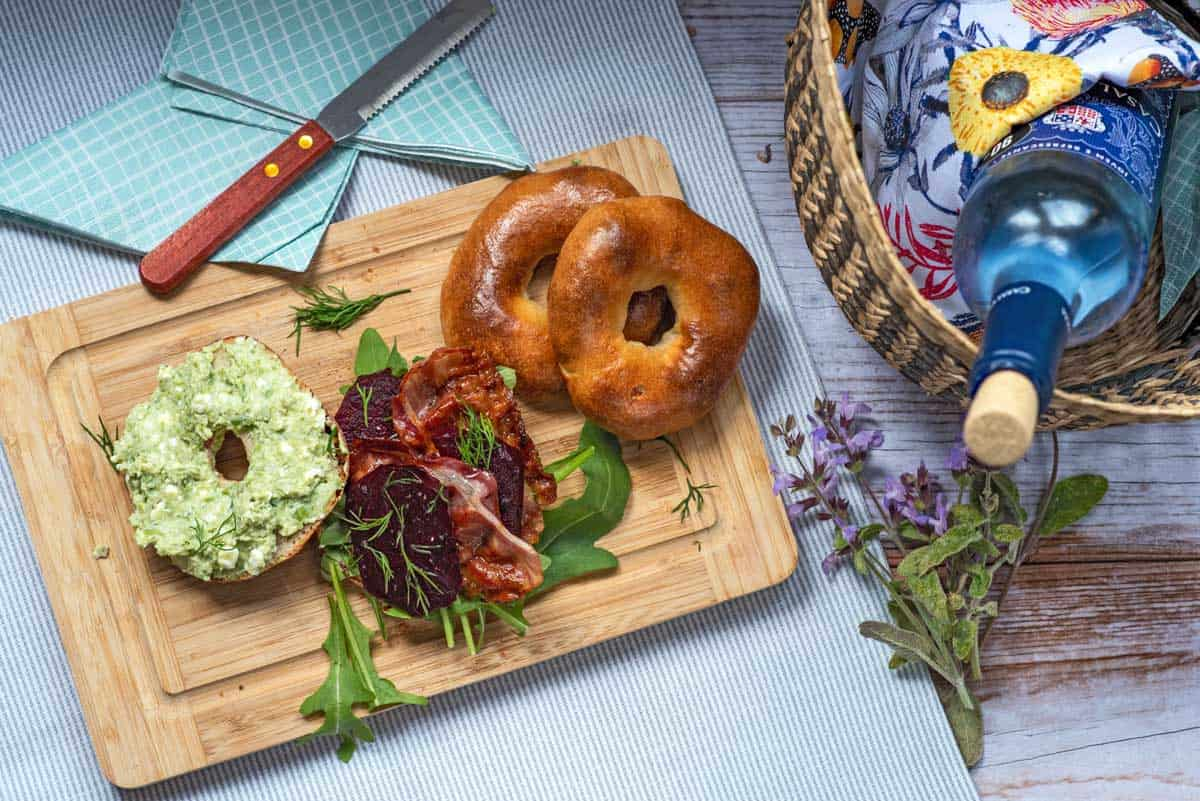 Open bagel with pea puree spread on one side and beets and bacon on the bottom half.