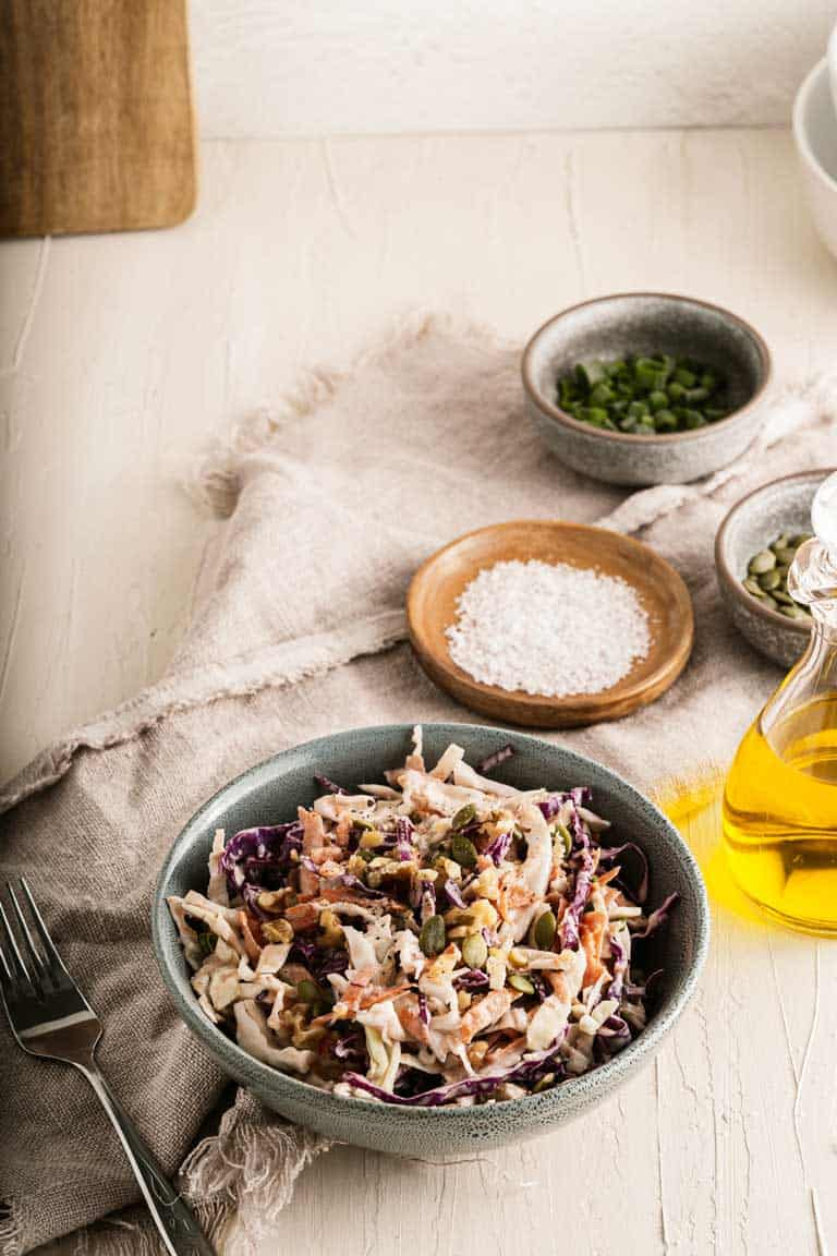 Bowl of crunchy coleslaw on atable surrounded by ingredients.