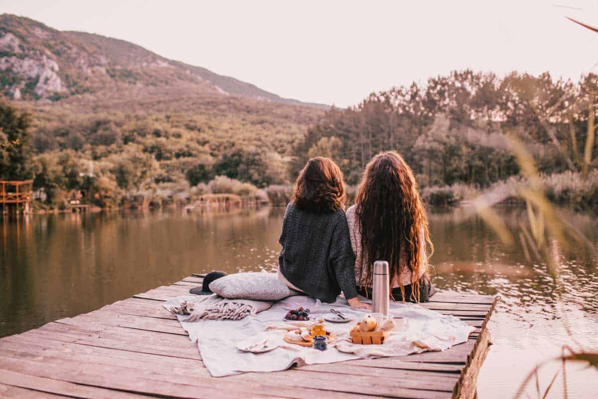2 girls having a picnic in autumn on a dock by a lake.