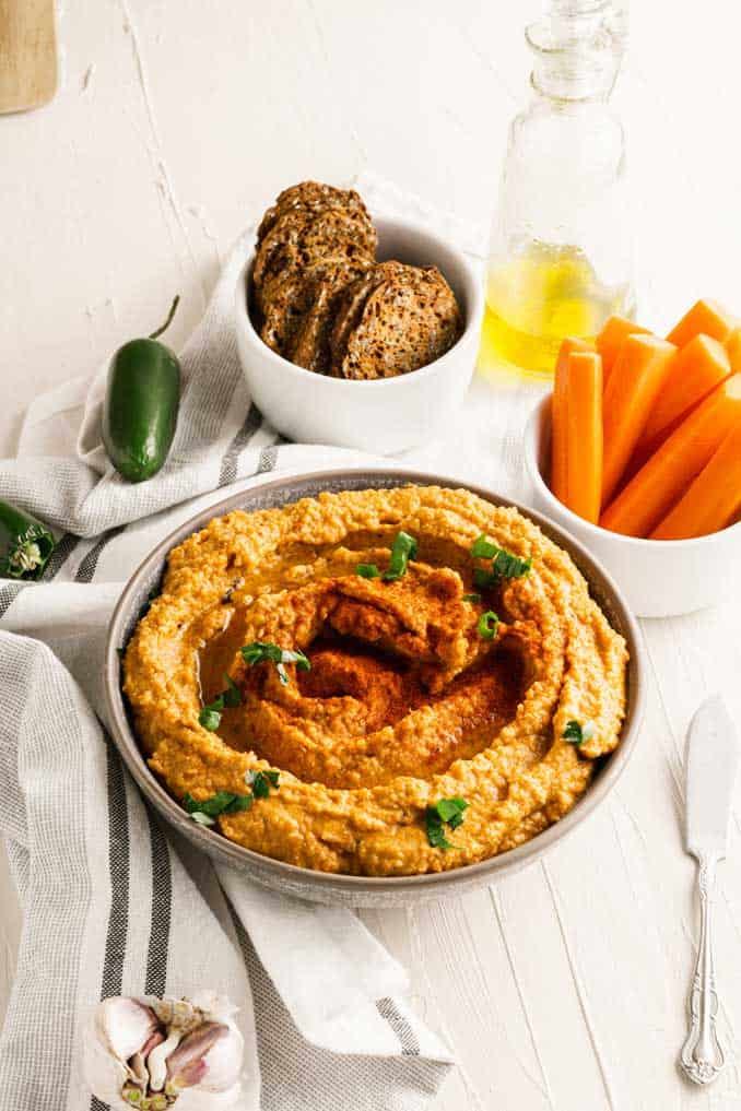 Bowl of roasted red pepper hummus with chipotle with bread crisps and carrot sticks.