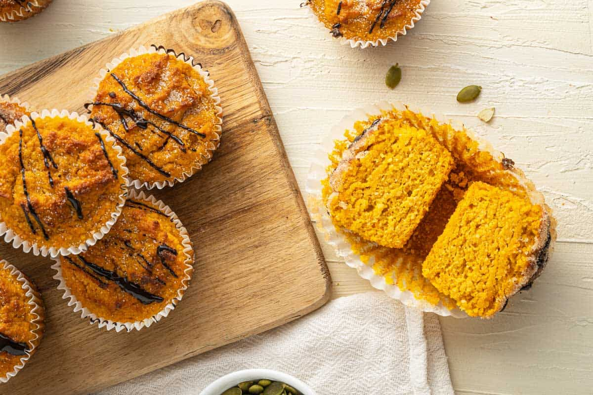 Low carb keto pumpkin muffins on a serving board with one muffin cut in half.