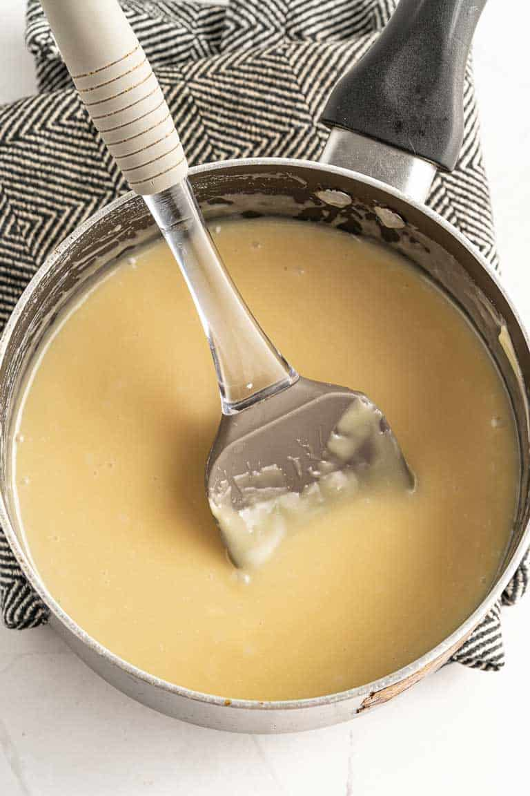 Mixing white chocolate fudge ingredients in a saucepan while they melt.