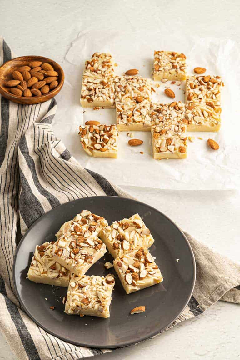 Squares of white chocolate fudge with almonds on a plate and on baking paper.