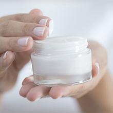 Female hand holding moisturizer in hand, horiztonal