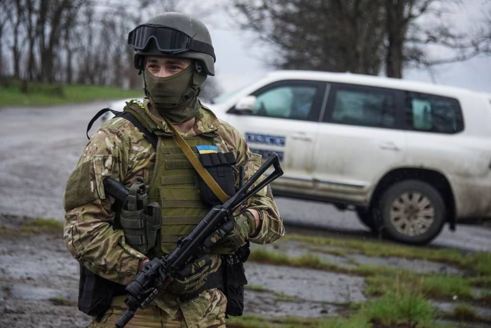 A Ukrainian soldier guards OSCE observers near the village of Shyrokyne, eastern Ukraine, Sunday, April 19, 2015. Russia has sent arms and drone aircraft into eastern Ukraine and is concentrating troops along the tense border, a buildup that is raising concern about a new escalation in the conflict, the U.S. State Department said Wednesday, April 22, 2015.