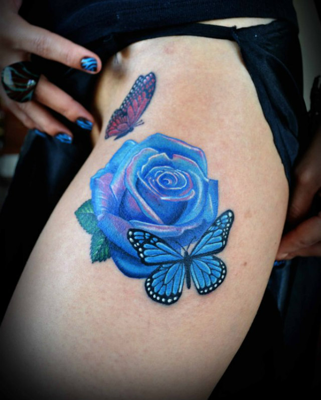 Cool Blue And Red Light Color Ink Rose Tattoo On Girl's Thigh