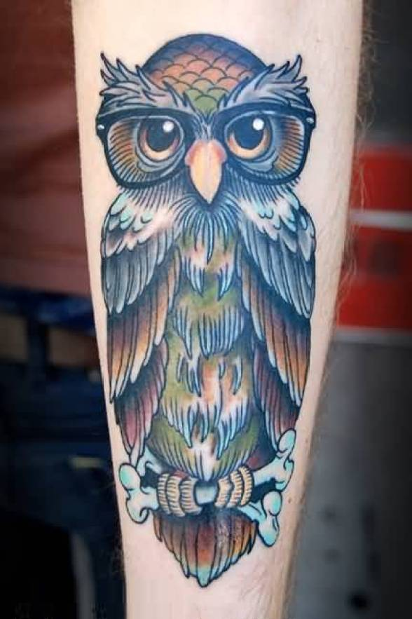 coolest blue green and brown color ink animated owl tattoo on boy's sleeve for boys only made by expert
