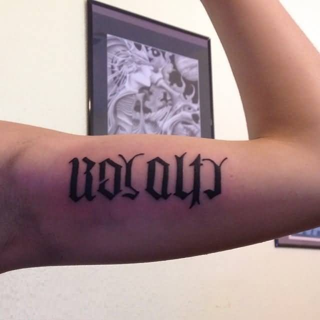 cute black color ink ambigram tattoo on bicep for boys only