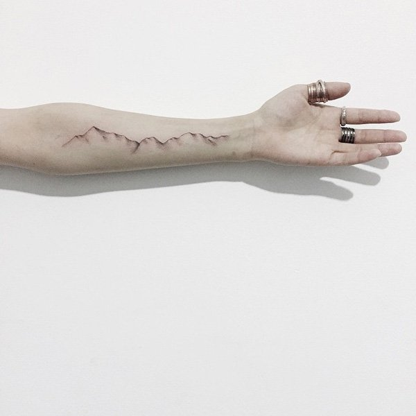 dashing mountain tattoo on wrist With Black ink For Man And Woman