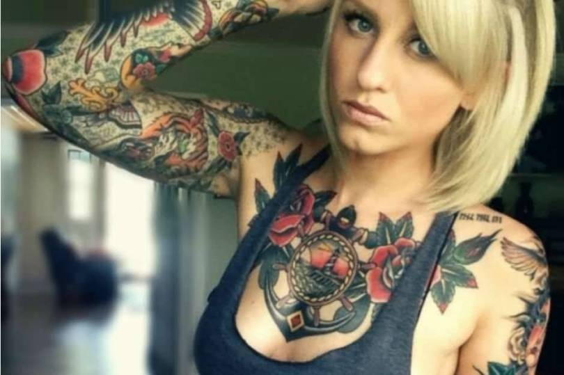 extremely red and gray color ink anchor tattoo on girl chest and full arm made by expert