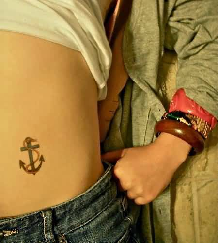 horrible blue and black color ink anchor tattoo on girl's back ribs side