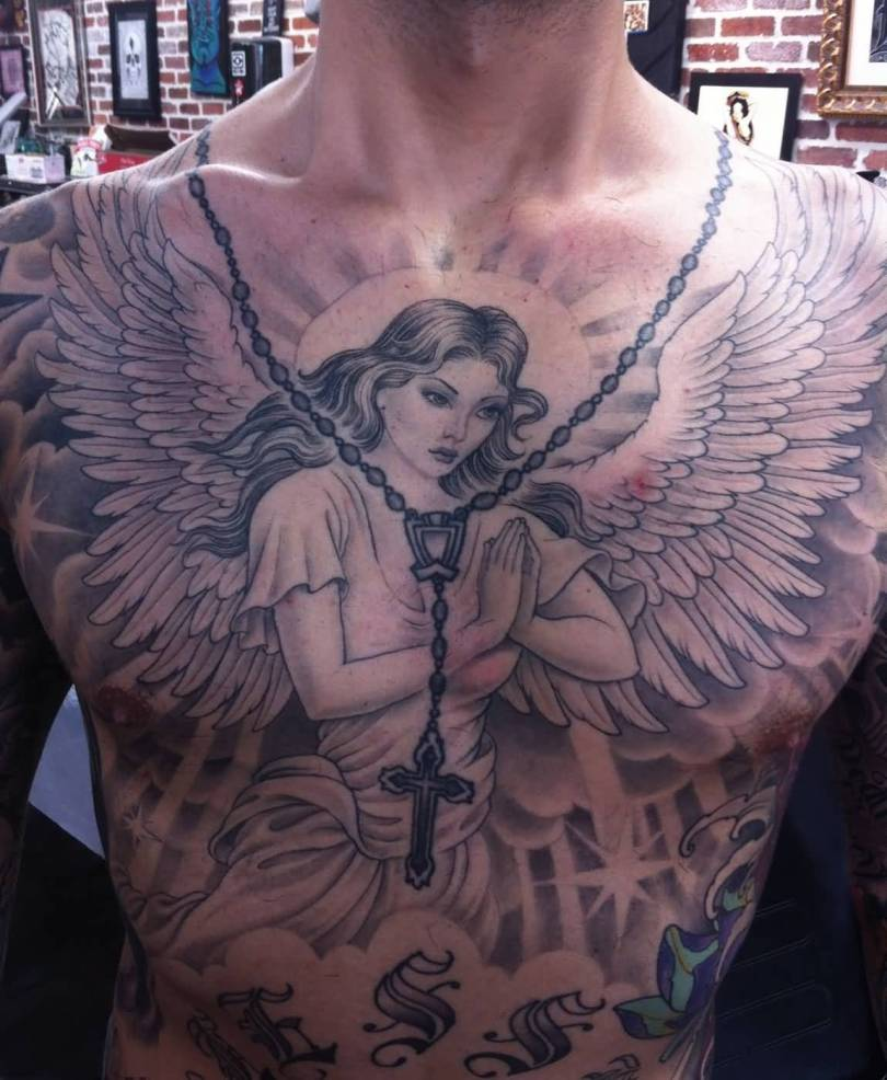 inspirational black color ink angel tattoo on boy chest for boys made by expert artist Angel Chest Tattoo