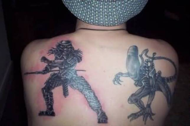 Two Alien Fighting Tattoo On Mans Back For Man
