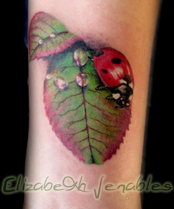 Brilliant Green White Black And Red Color Ink Lady Bug Tattoo On Arm For Girls