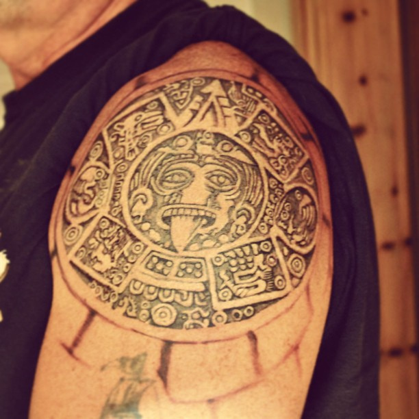 Extremely Black And Red Color Ink Aztec Calendar Tattoo On Biceps For Boys