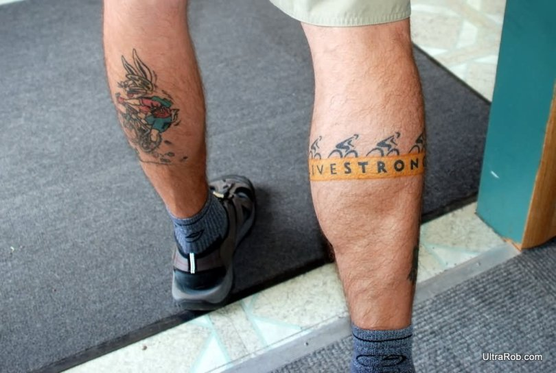 Incredible Blue Red And Black Color Ink Live Strong Bike Tattoo On Leg For Man