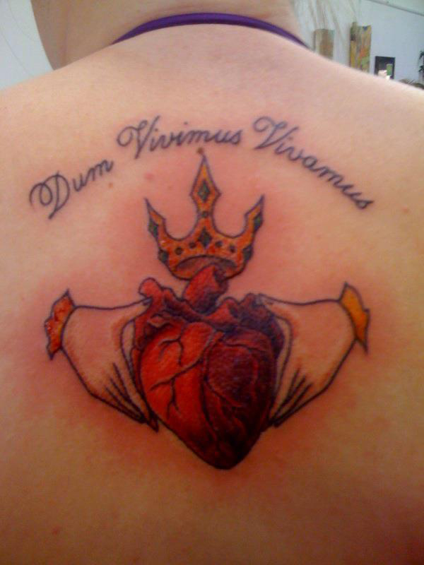 Inspirational Blue Yellow Red And Black Color Ink Claddagh Tattoo On Back For Girls