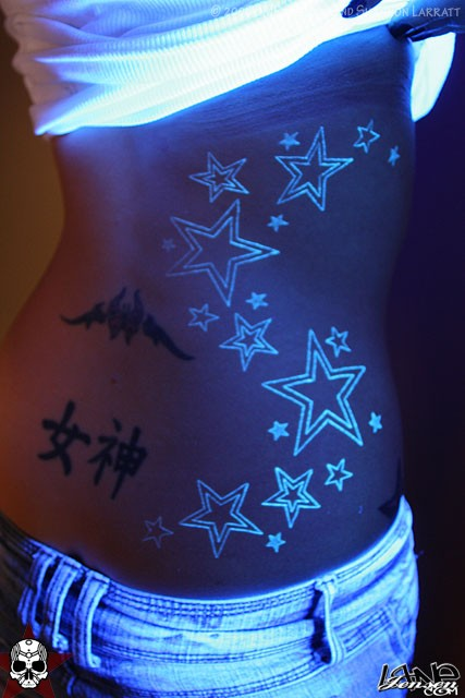 Lovely Black And Green Color Blacklight Stars Tattoo On Rib Side For Girls