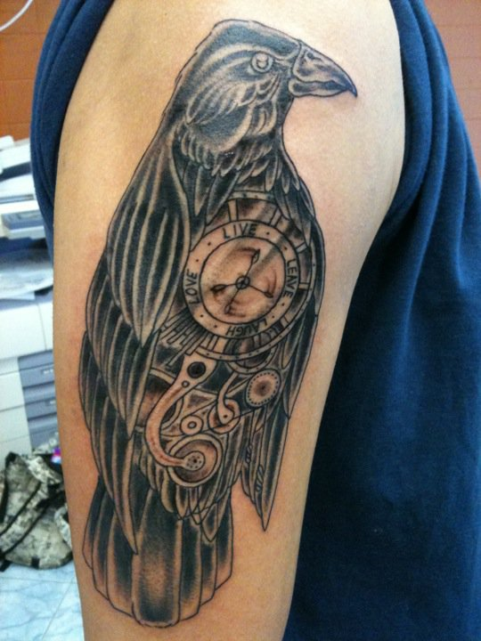 Mind Blowing Black Color Ink Clockwork Crow Tattoo On Arm For Boys