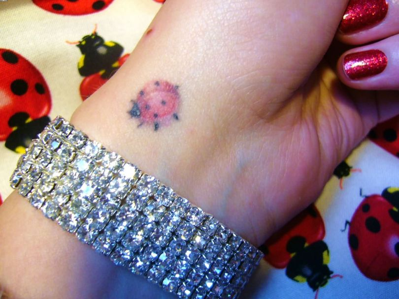 Most Cute Sitting Ladybug On Wrist Tattoo With Colorful Ink