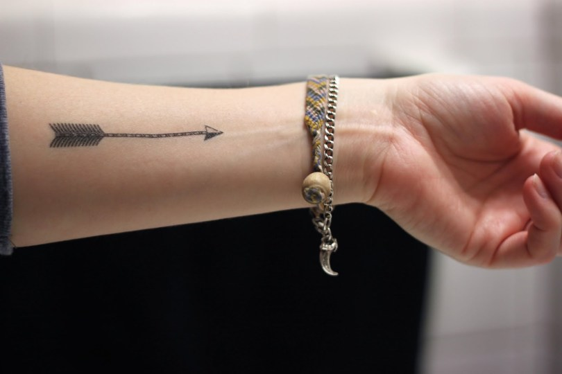 Passionate Black Color Ink Arrow Tattoo Near Wrist For Boys