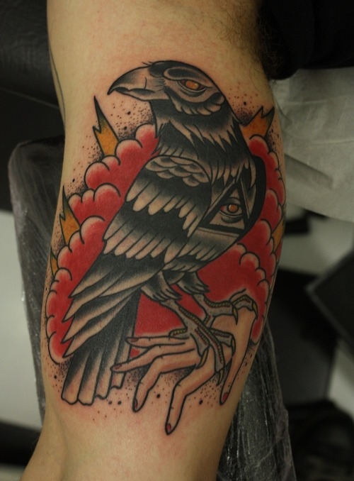 Popular Red And Black Color Ink Clouds Behind Eye Crow Tattoo For Boys